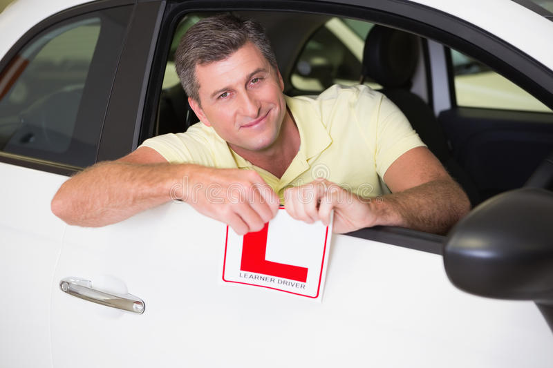 Cheerful male driver tearing up his L sign. At new car showroom stock image