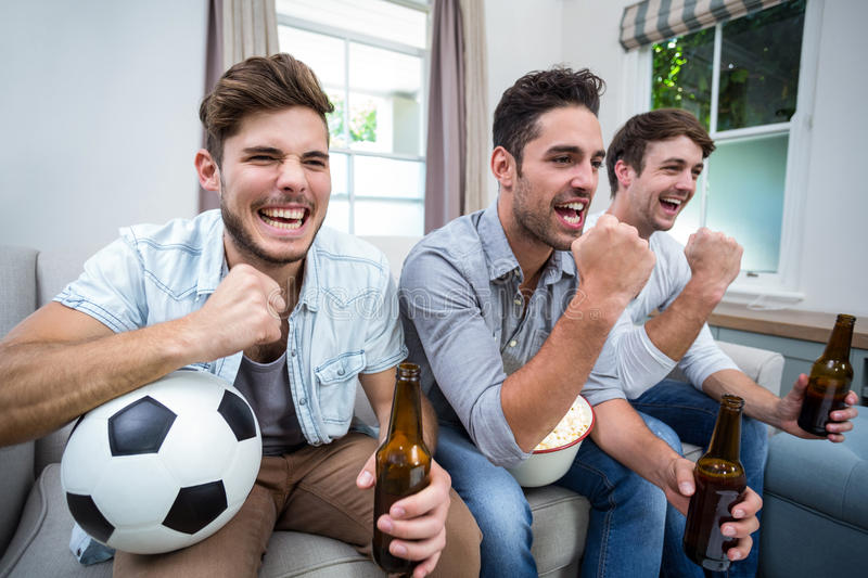 Cheerful male friends watching soccer match on TV stock photos
