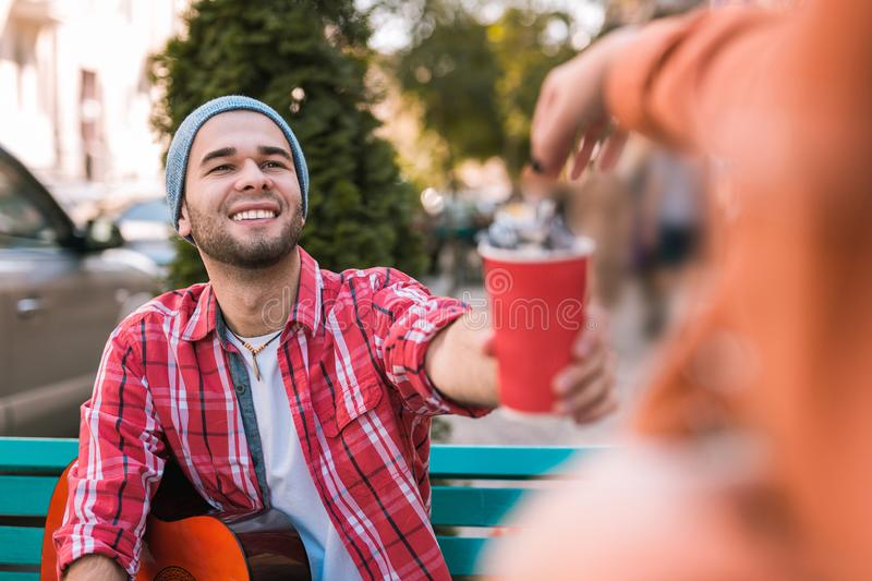 Cheerful male guitarist picking up money for play stock images