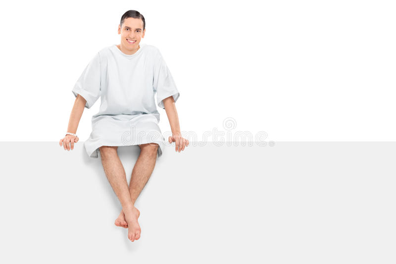 Cheerful male patient sitting on a blank panel stock image
