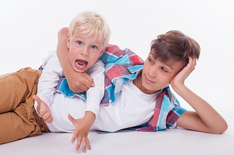 Cheerful male siblings are spending time together. Cute two brothers are lying on flooring and making fun. The elder boy is embracing the neck of his brother and stock photos