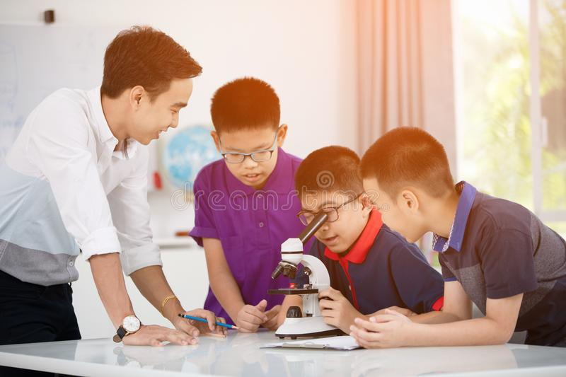Asian boy examining preparation under the microscope royalty free stock image