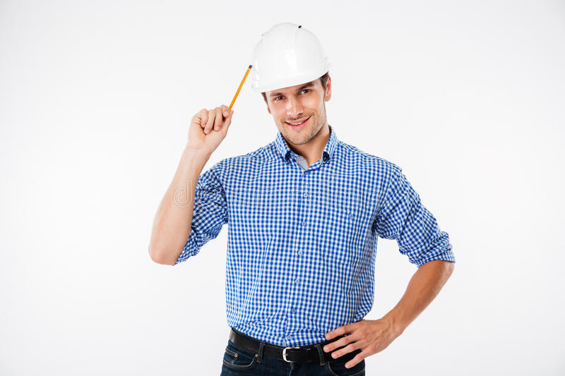 Cheerful man architect in hard hat standing and holding pencil royalty free stock image