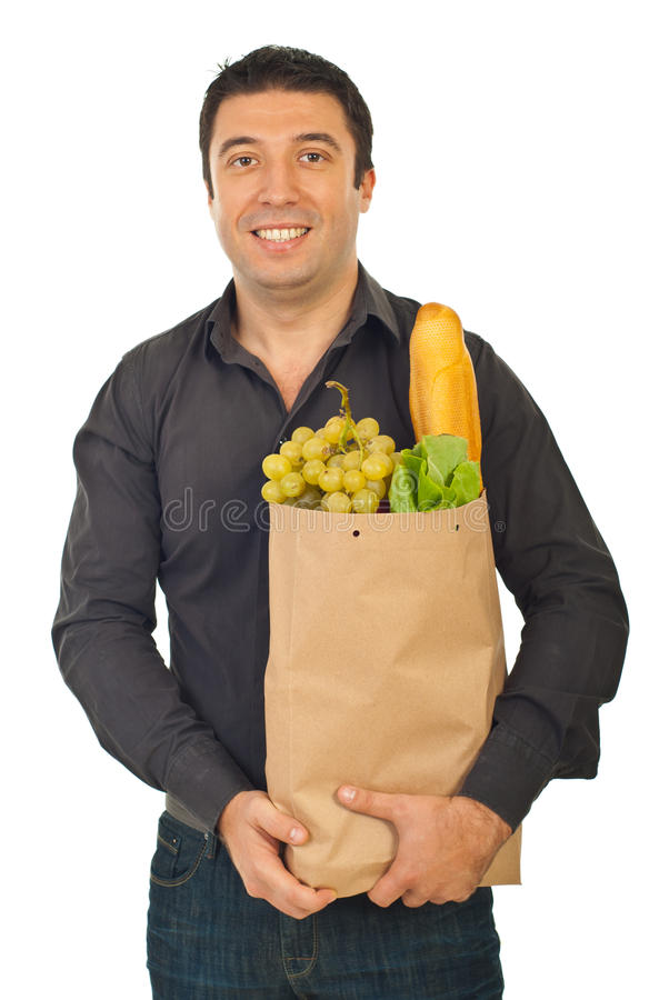 Cheerful man carrying shopping bag with food stock image
