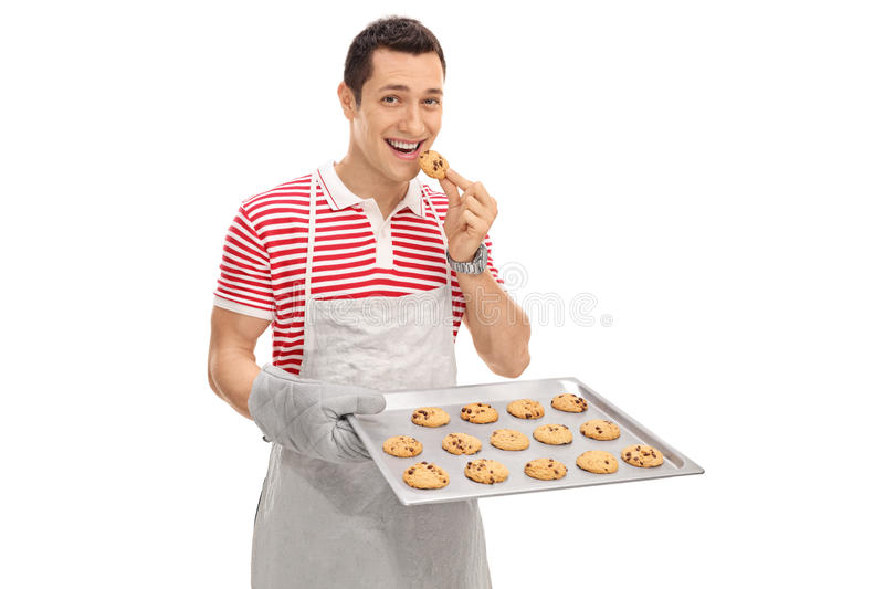 Cheerful man eating cookies. Cheerful man eating freshly baked chocolate chip cookies isolated on white background royalty free stock image