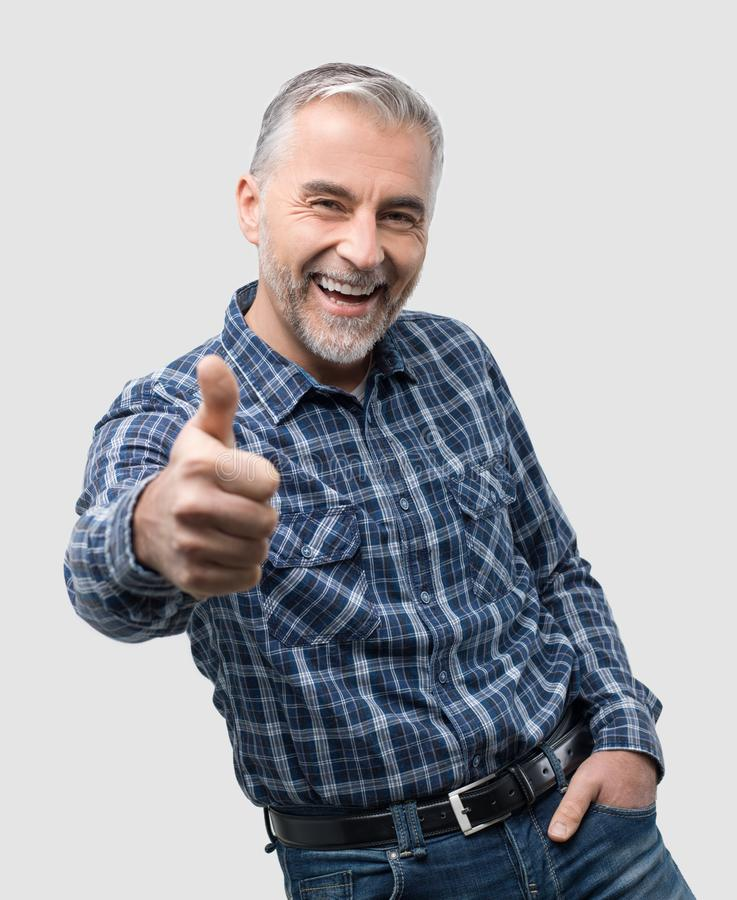 Cheerful man giving a thumbs up stock image