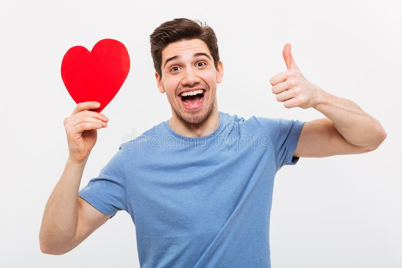 Cheerful man holding paper heart and showing thumb up. Cheerful man in t-shirt holding paper heart and showing thumb up while looking at the camera over grey royalty free stock photography