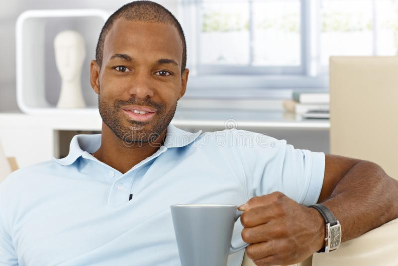 Cheerful man at home having tea stock photos