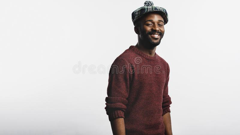 Portrait of man wearing cap. Cheerful man isolated on white background wearing a scottish cap. e view of african american man in winter woollen clothes looking royalty free stock images