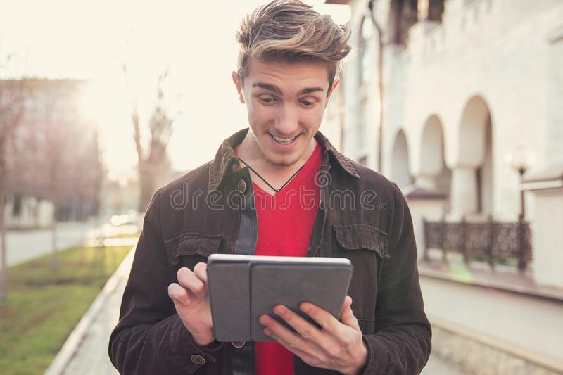 Cheerful man in jacket standing outdoors and surfing tablet happily royalty free stock photography