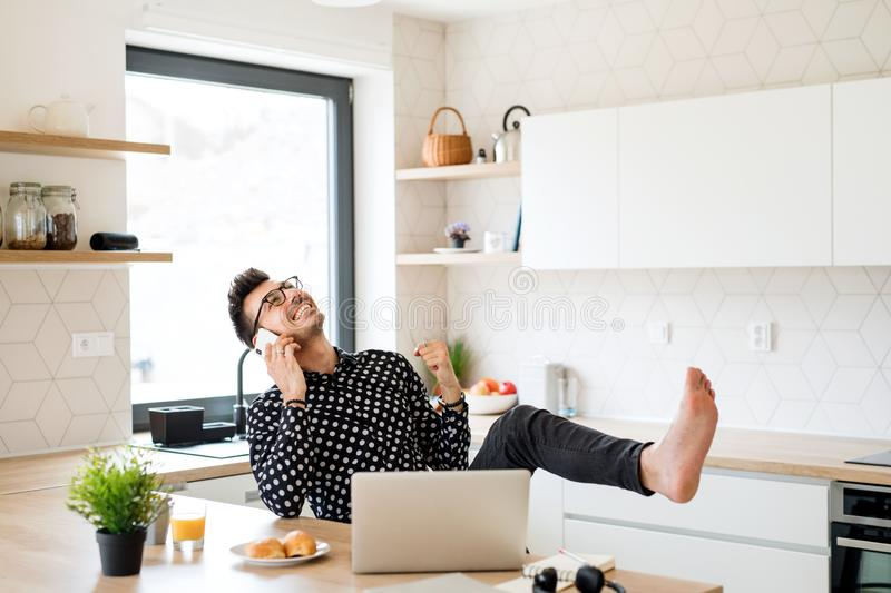 Cheerful man with laptop and smartphone sitting in kitchen, making a phone call. stock photos