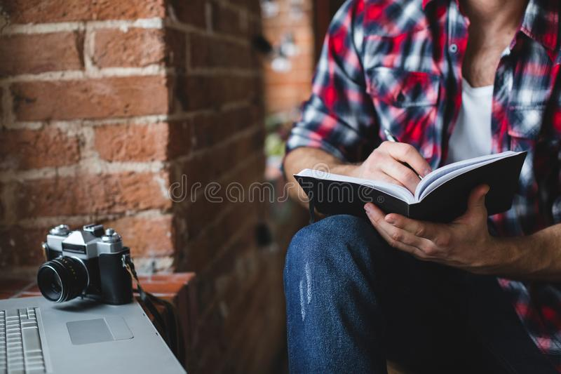 Cheerful man with a laptop writes in a notebook close-up. Freelancer stock images