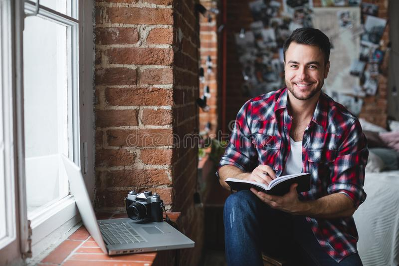 Cheerful man with a laptop writes in a notebook. Freelancer royalty free stock photos