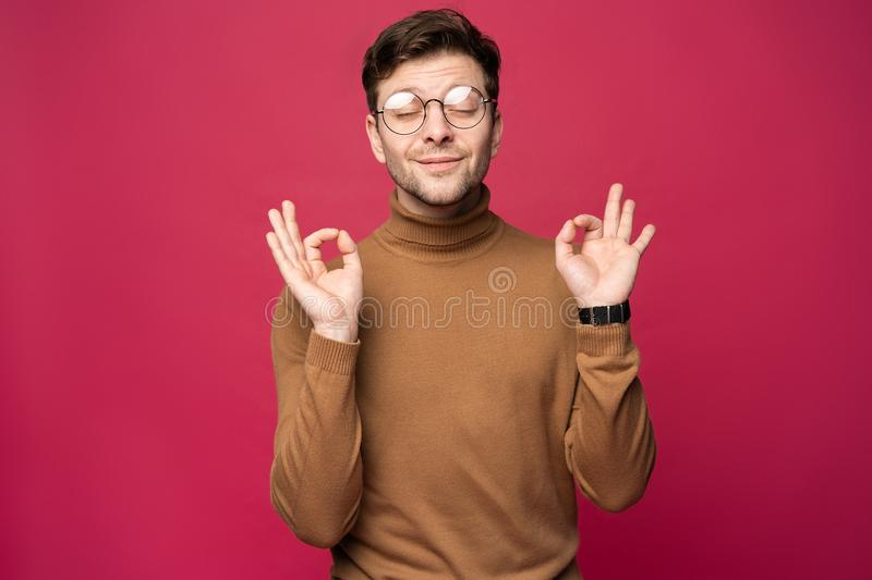 Cheerful man laughing and looking at camera. Portrait of a happy young man standing over pink background royalty free stock photo