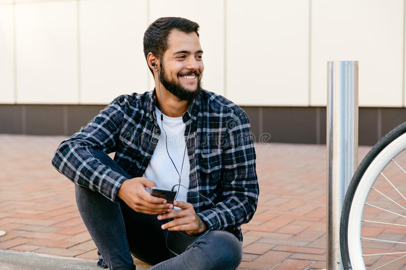 Cheerful man listening to music in earphones, sitting outdoors stock photo