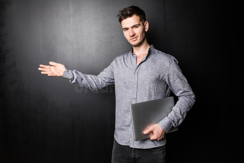 Cheerful young man with open palm and using laptop over black background royalty free stock photo
