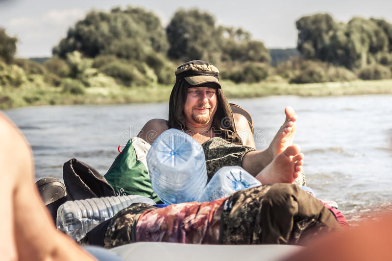 Cheerful man with pleasure smile and closed eyes relaxing outdoors during summer holidays. Cheerful young man with pleasure smile and closed eyes relaxing royalty free stock image