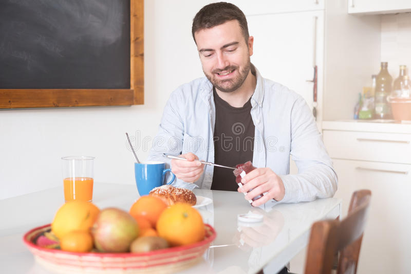 Cheerful man preparing breakfast in the morning royalty free stock photo