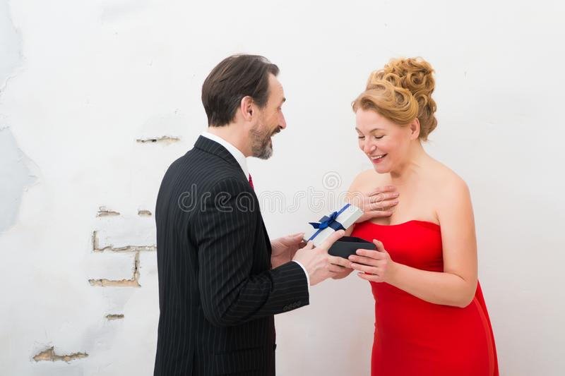 Cheerful man presenting a gift to his amused wife stock photo