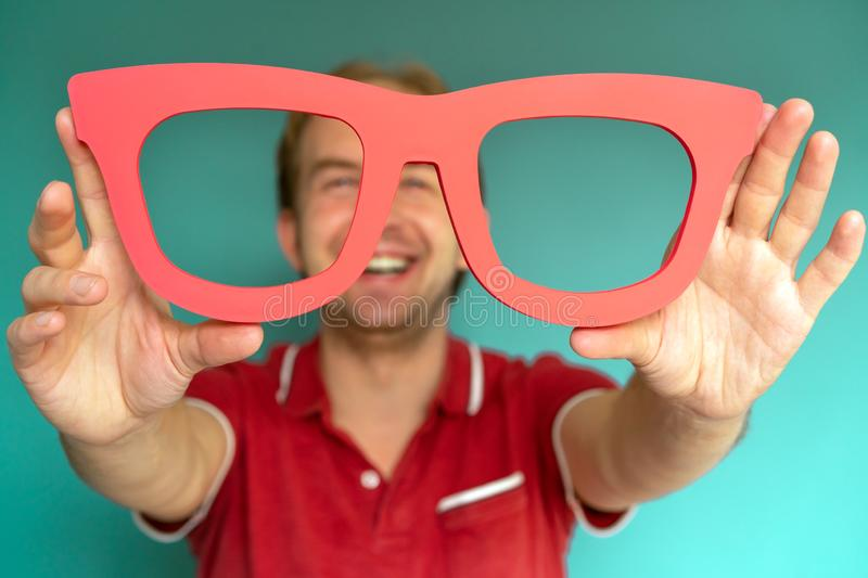 Cheerful man in a red shirt holds big red glasses. stock photography