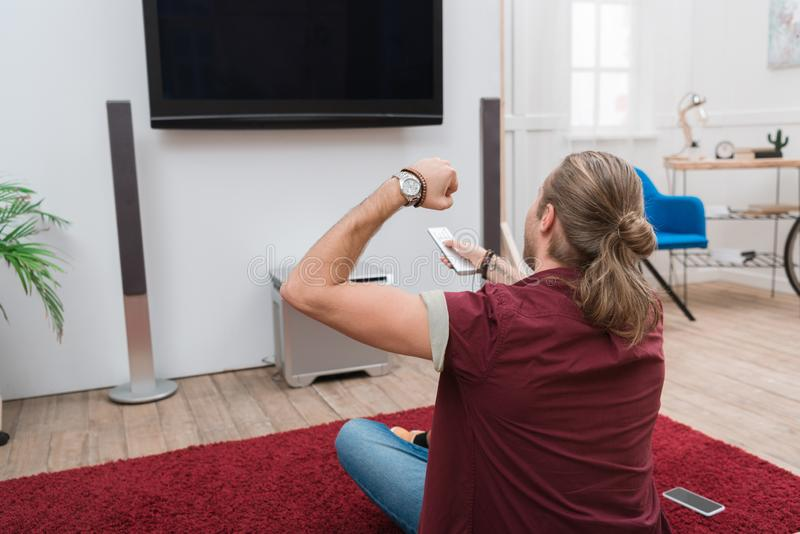 Cheerful man with remote control gesturing and watching tv. At home royalty free stock photos