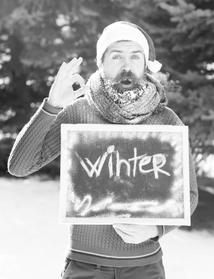 Cheerful man in santa claus hat, bearded hipster with beard and moustache covered with white frost, gives ok gesture stock photography