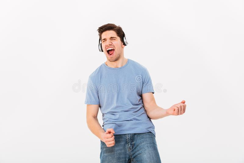 Cheerful man with short dark hair listening to music via earphones and acting like guitar player, isolated over white background stock images