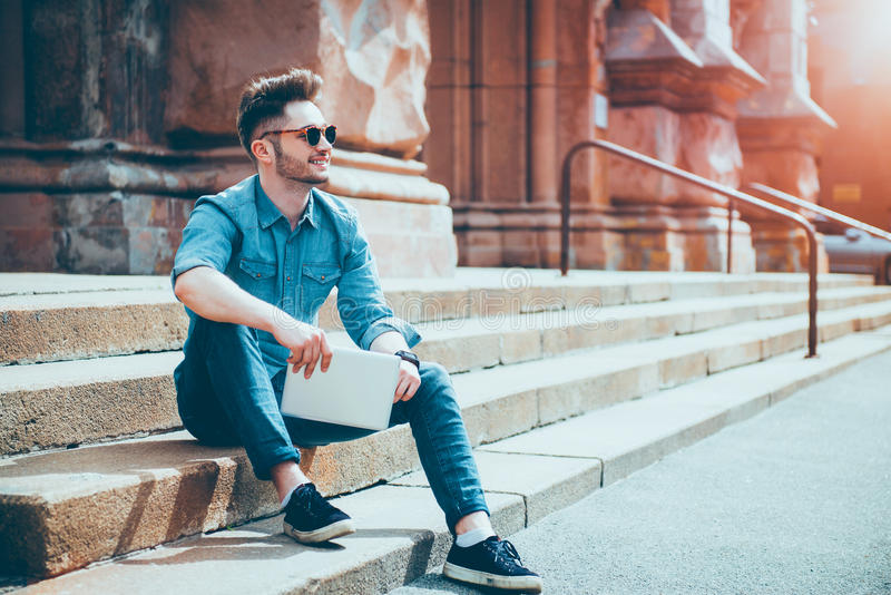 Cheerful man sitting on the footsteps royalty free stock photos