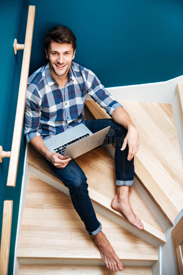 Cheerful man sitting on stairs at home and using laptop stock photos