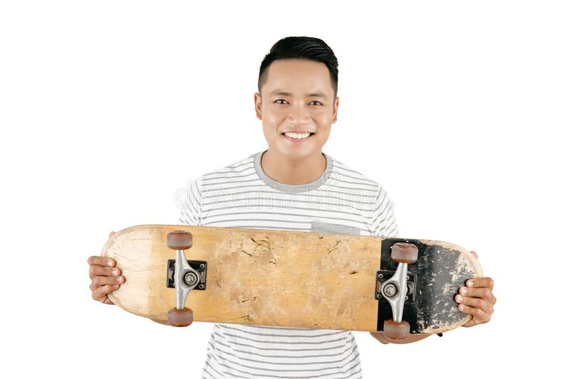 Cheerful Man With Skateboard. Portrait of handsome Asian guy in casual T-shirt holding skateboard and smiling at camera joyfully against white background royalty free stock photography