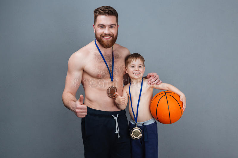 Cheerful man and son with golden medals holding basketball ball royalty free stock images