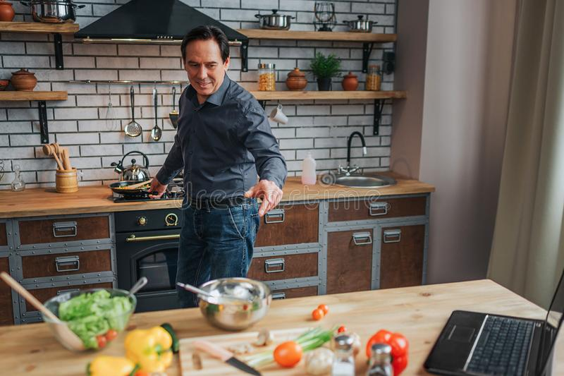 Cheerful man stand at stove and cook food in kitchen. He look at table and reach hand to it. Guy smile. stock images