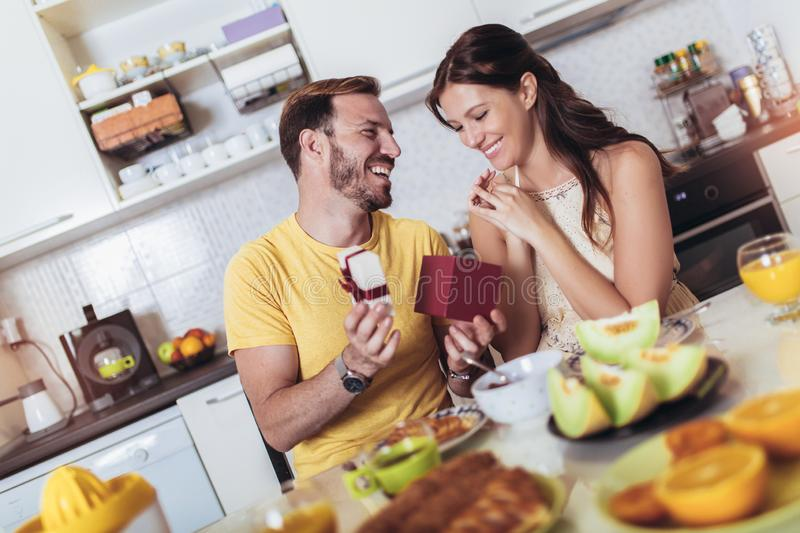 Cheerful man surprising his girlfriend with a gift at home in the kitchen while breakfast. Happy cheerful men surprising his girlfriend with a gift at home in royalty free stock photography
