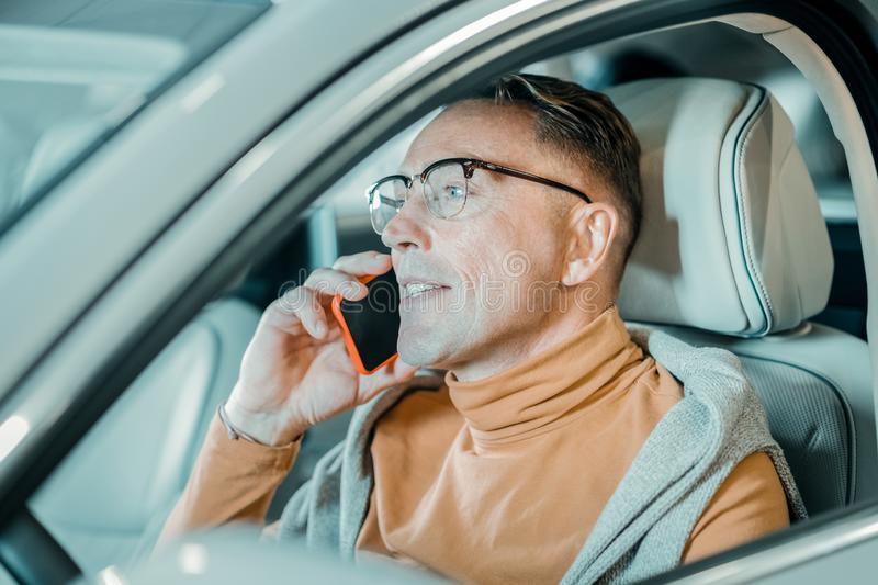 Cheerful man talking with his wife on the phone. Telling about new car. Cheerful man wearing eyeglasses sitting on the drivers seat and talking with his wife on royalty free stock image