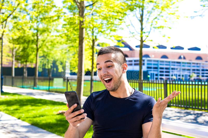 Joyful hipster guy having online video call via cellphone, sitting in park royalty free stock photography