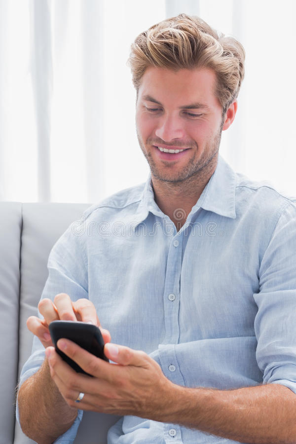 Cheerful man using his smartphone on a couch stock photos