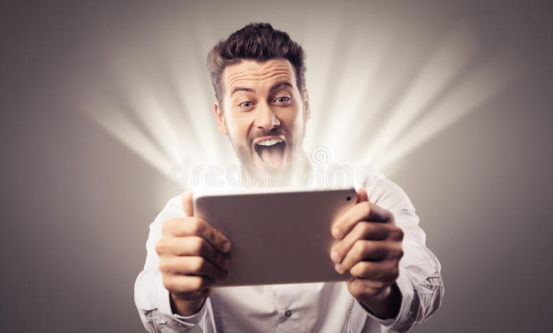 Cheerful man watching videos on tablet royalty free stock images