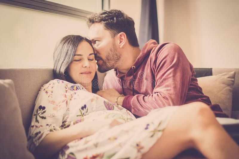 Cheerful man and woman caucasian in leisure activity at home smile and enjoy life waiting a new baby to complete the couple and. Couple in love at home lay down stock photo