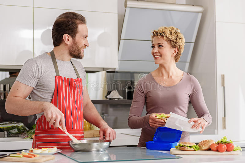 Cheerful man and woman preparing breakfast at home stock photography