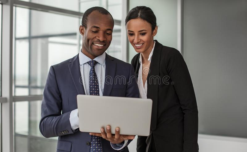 Cheerful man and woman are standing in office with device. Creating new ideas. Portrait of positive young business partners wearing formal clothes are standing stock images