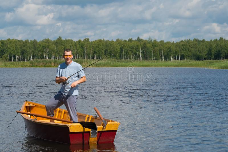 A cheerful man in yellow glasses, in a boat with oars, in the center of the lake, holds a fishing pole to catch a big fish, in the. Background of a beautiful stock images