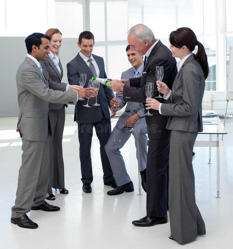 Cheerful manager serving Champagne to his team royalty free stock photo