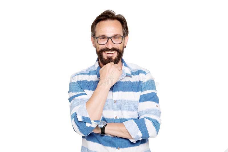 Positive bearded man keeping his fist under chin. Cheerful mature bearded man expressing happiness while keeping his fist under chin and showing sincere emotions royalty free stock photo