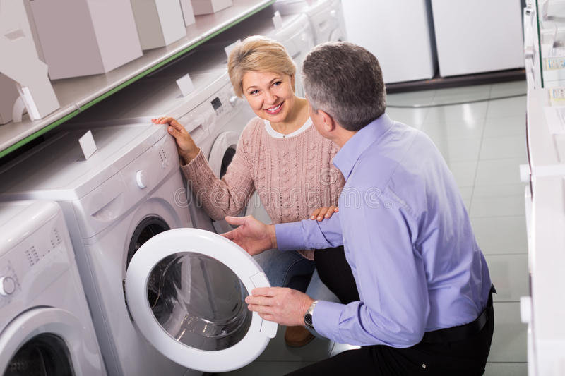 Cheerful mature couple chooses washing machine for their house i royalty free stock photography