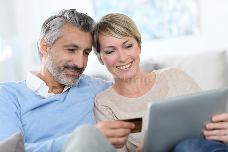 Cheerful mature couple shopping on tablet stock image