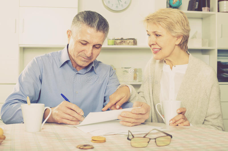 Cheerful mature couple at table attentively study documents royalty free stock images