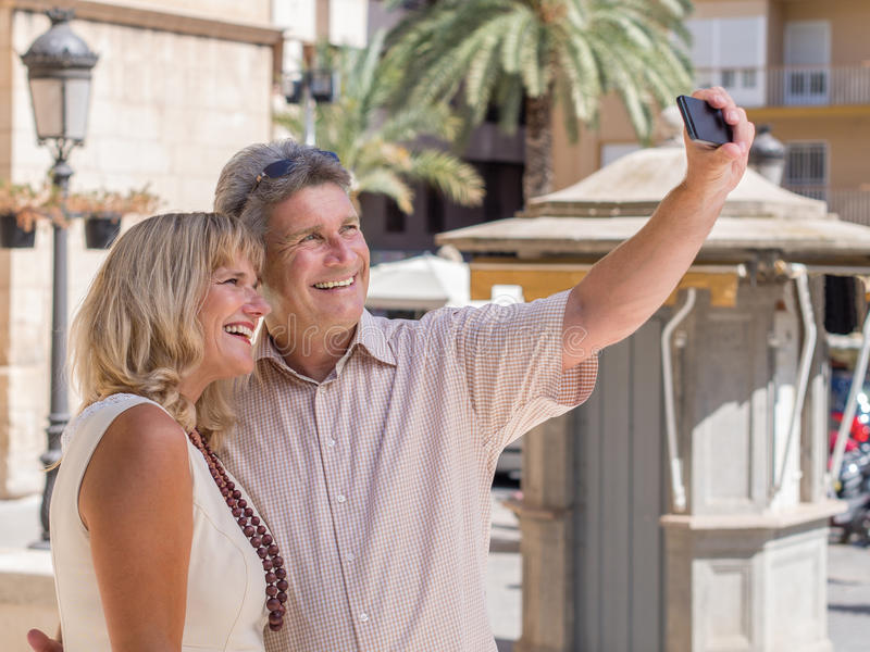 Cheerful mature couple taking selfie pictures of themselves in holidays royalty free stock photos