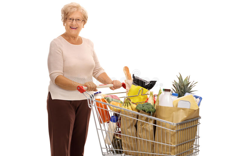 Cheerful mature lady with shopping cart. Cheerful mature lady with a shopping cart full of groceries isolated on white background stock image