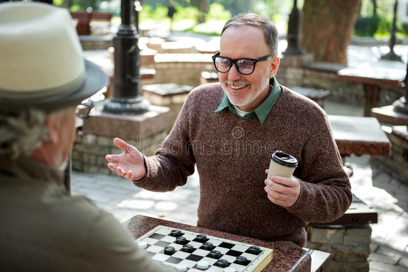 Cheerful mature male pensioners entertaining with draughts in park stock photos