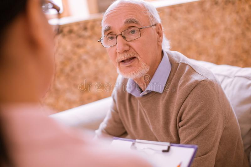 Cheerful mature man communicating with his helper royalty free stock image